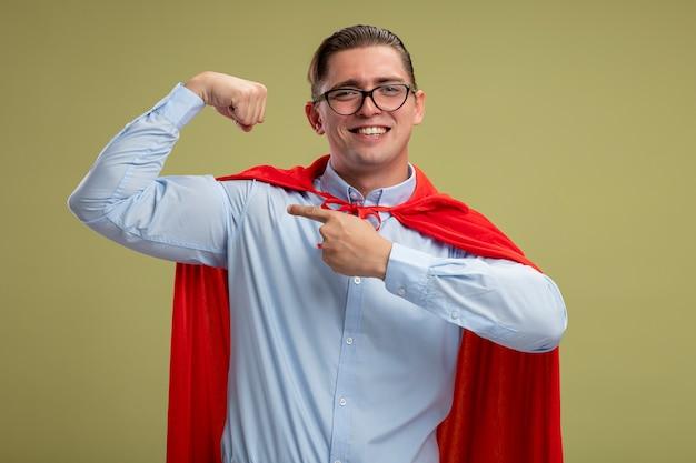 赤いマントと眼鏡をかけた自己満足のスーパーヒーローのビジネスマンが上腕二頭筋に人差し指で握りこぶしを上げ、明るい背景の上に元気に立って笑顔の強さを示しています