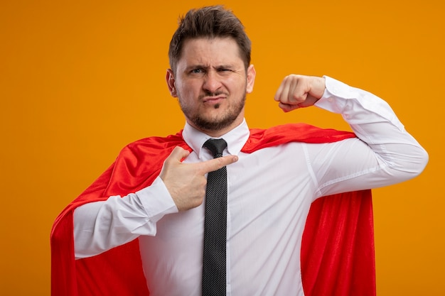 オレンジ色の背景の上に立って自信を持って見える強さを示す上腕二頭筋で人差し指で指さし拳を上げる赤いマントの自己満足のスーパーヒーロービジネスマン