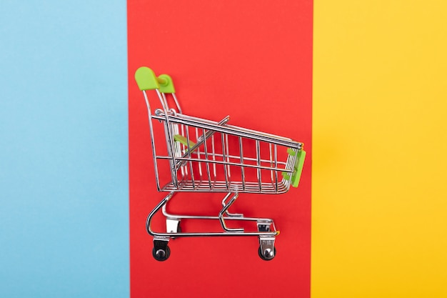 Self-service supermarket trolley cart with green handle on colorful background