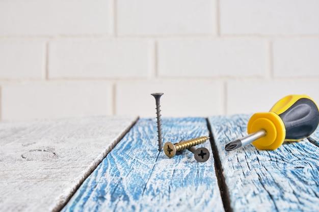 Саморез и отвертка на деревянной доске фоновое пространство для копирования