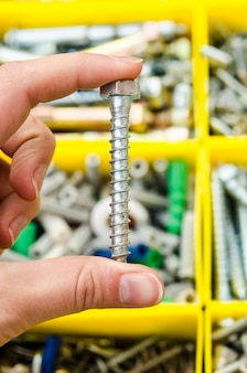 Self-tapping screw in hand on the background of tools.