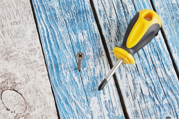 Self-tapping screw and screwdriver on wooden board background copy space