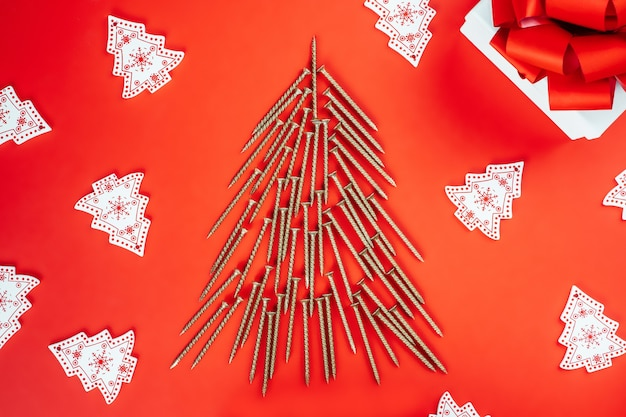 셀프 태핑 나사, 크리스마스 트리 모양으로 배치, 나무 크리스마스 트리 장식, 빨간색 배경에 선물 상자