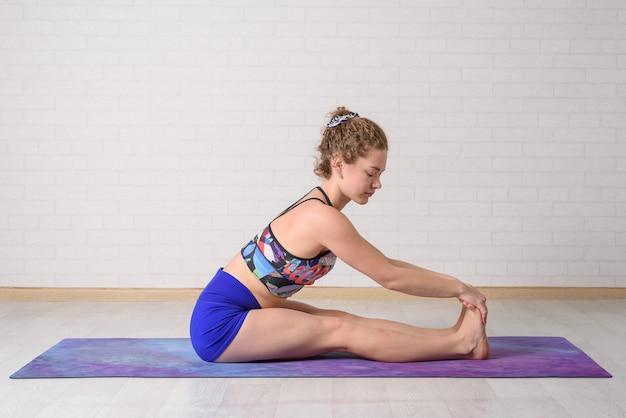 Самостоятельная йога тренировки дома. молодая красивая девушка занимается йогой дома.