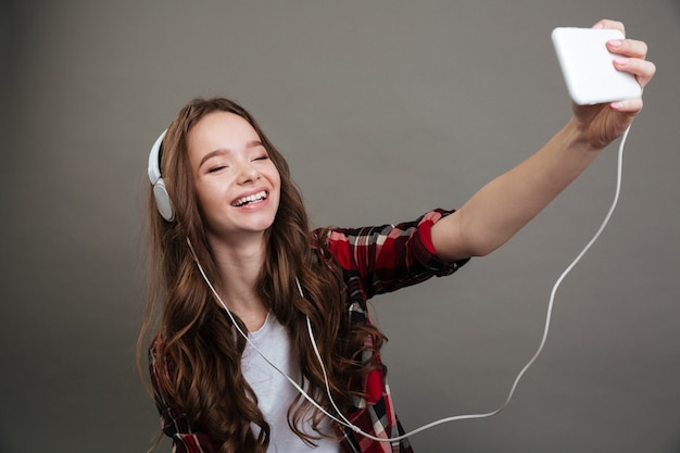 Selfieを取って、ヘッドフォンで音楽を聴く陽気な女の子10代