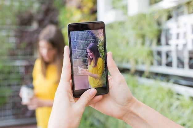 携帯電話でselfieを取る2人の美しい女性。 。 1つはコーヒーカップを持っています。彼らは笑っている 。アウトドアライフスタイルと友情