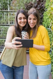 携帯電話でselfieを取っている2人の美しい女性。 1つはコーヒーカップを持っています。彼らは笑っている。アウトドアライフスタイルと友情の概念