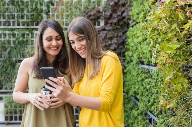 携帯電話でselfieを取っている2人の美しい女性。緑の背景。 1つはコーヒーカップを持っています。彼らは笑って携帯電話で情報を検索しています。アウトドアライフスタイルと友情