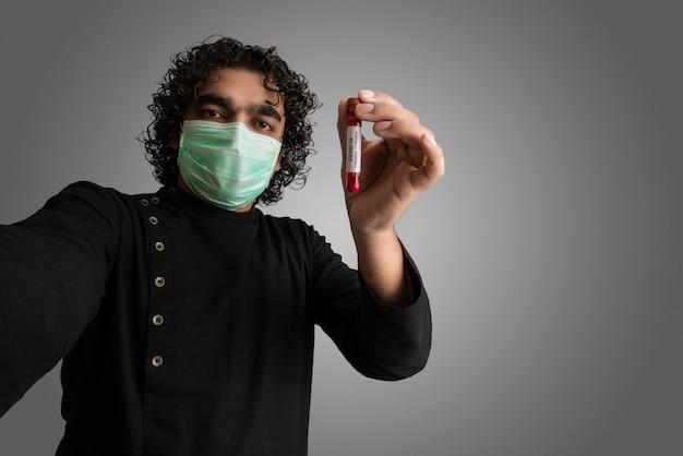 Молодой человек принимая selfie с пробиркой с пробой крови для анализа коронавируса или 2019-ncov.