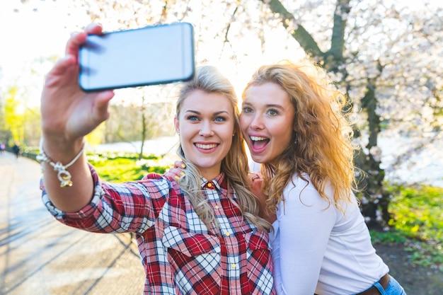 ロンドンの公園で、selfieを取っている2人の女性