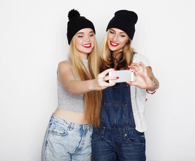 携帯電話でselfieを取る2人の若い女性