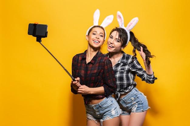 かわいいイースターのウサギの耳を着て、スティックを使用してselfieを作る2人の若い女性