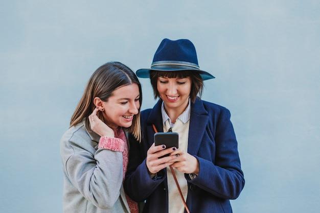携帯電話でselfieを取ってスタイリッシュな服を着て屋外の2人の友人