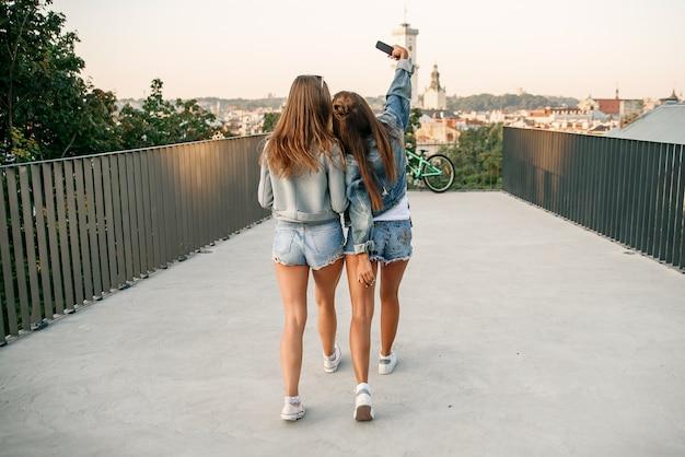 夏の晴れた日に歩きながらスケートボードに座っているときにスマートフォンでselfieを取る2人の女性の親友。屋外。