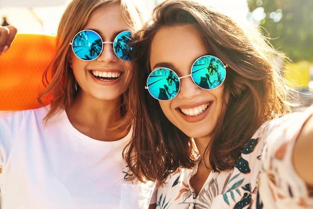 Selfieを取って夏流行に敏感な服で2人の若い女性のスタイリッシュなヒッピーブルネットとブロンドの女性