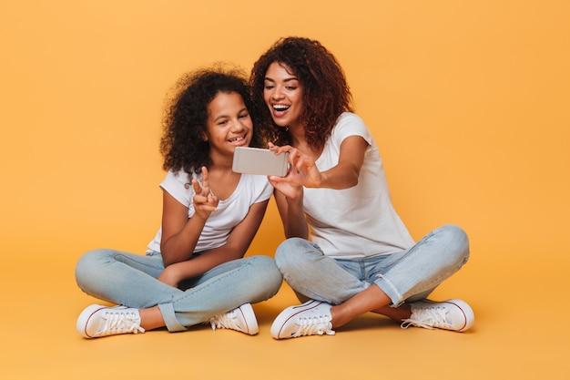スマートフォンでselfieを取って2つのうれしそうなアフロアメリカンの姉妹の肖像