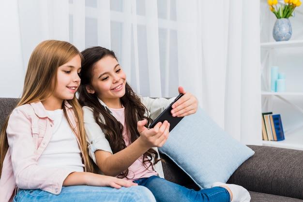 自宅で携帯電話にselfieを取って2つの笑みを浮かべて女友達