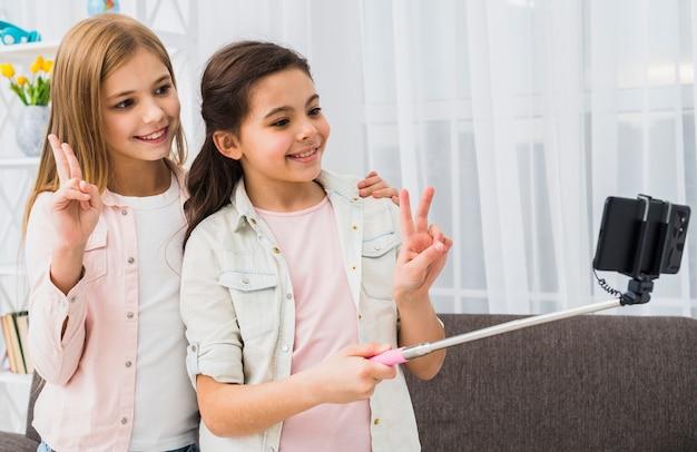 スマートフォンで自宅でselfieを取って平和のジェスチャーを作る2つの幸せな女友達