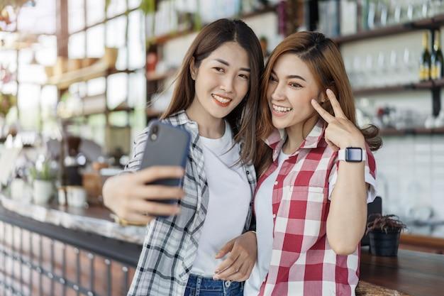 スマートフォンでselfieを取って2つの陽気な女性