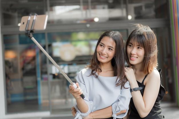 ショッピングモールでselfieを作る陽気な2つの笑顔のガールフレンドの肖像画。