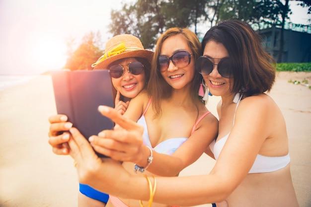 夏のビーチでリラックスして、スマートフォンでselfieを取って3つのアジアの女性
