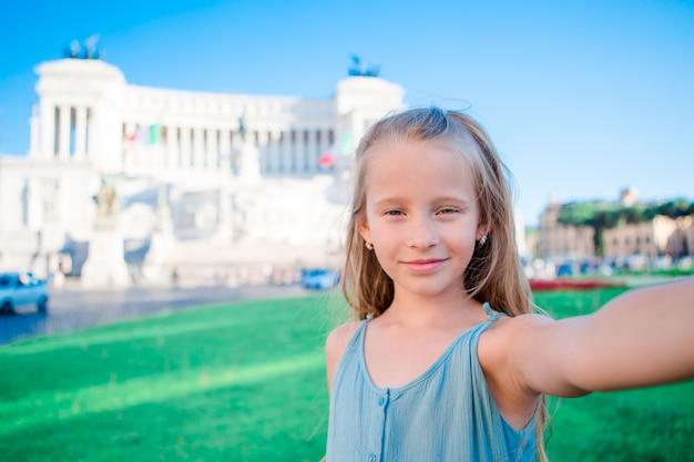 Прелестная маленькая девочка принимая selfie перед altare della patria, национальным памятником vittorio emanuele ii также известным как ii vittoriano, рим, италия.