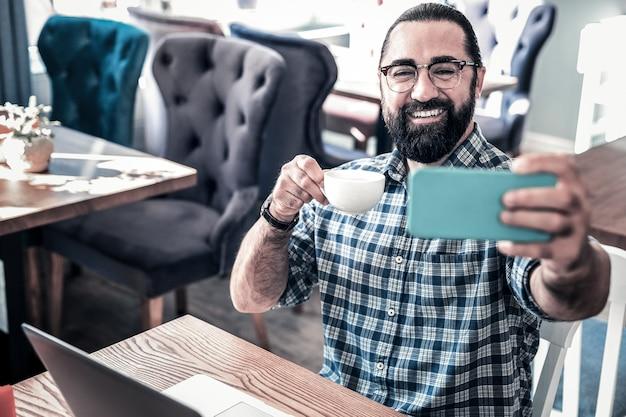 セルフィーとコーヒー。自撮り写真を作ったりコーヒーを飲んだりしてリラックスしたあごひげを生やした黒髪の男
