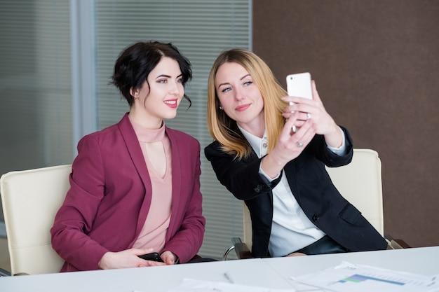 Селфи на работе. деловые женщины веселятся на офисной встрече, фотографируя себя.