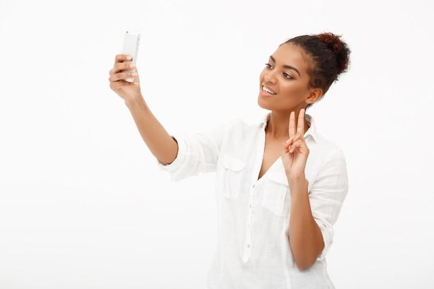 Портрет молодой африканской женщины делая selfie на белом backgrou
