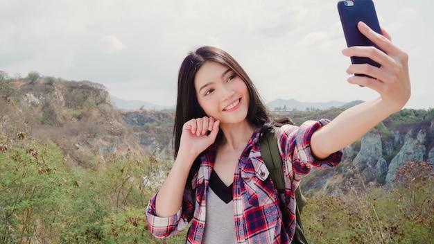 Азиатское selfie женщины backpacker на верхней части горы, молодая женщина счастливая используя мобильный телефон принимая selfie наслаждается праздниками на пешем приключении.