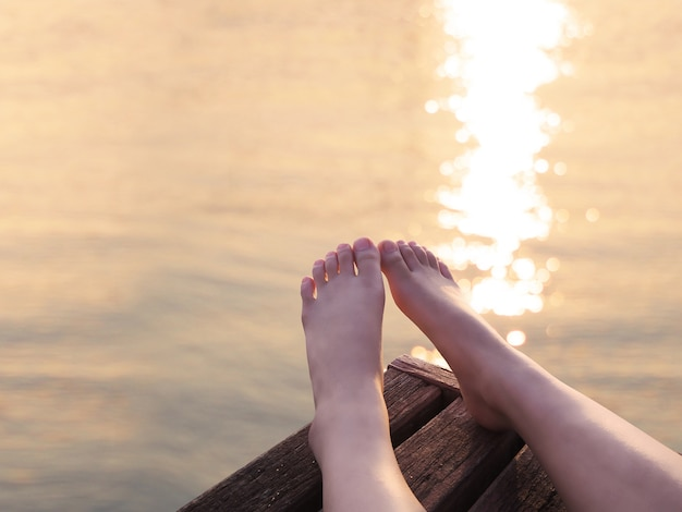 Selfie bare feet on wood background at sunset