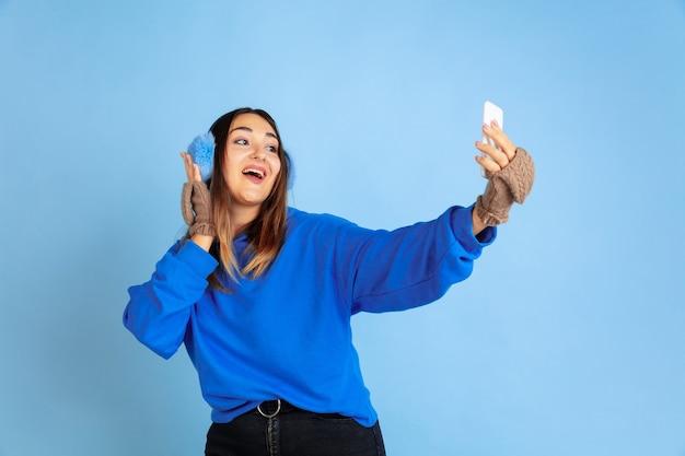 Селфи. портрет кавказской женщины на синем фоне студии. красивая женская модель в теплой одежде. понятие человеческих эмоций, выражения лица, продаж, рекламы. зимнее настроение, рождество, праздники.