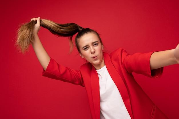 Селфи крупным планом фото довольно позитивной улыбающейся брюнетки маленькой девочки-подростка в модной красной куртке и белой футболке для макета, стоящего изолированно над красной фоновой стеной, смотрящей в камеру