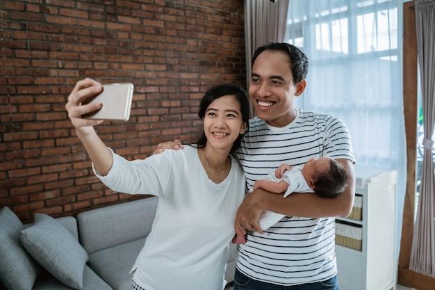 Selfieコンセプト、小さな赤ちゃんの娘を運ぶ陽気な家族