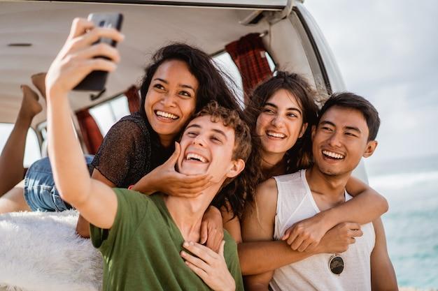 Selfieコンセプト、レトロなバンで後ろからボーイフレンドを抱き締める