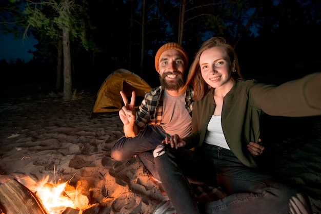 Selfie of couple camping at night by campfire
