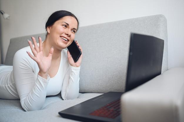 Молодая европейская независимая женщина звоня компьтер-книжка и телефон selfie или видео звонка на сером кресле во время карантина дома изоляции коронавируса. covid-19 пандемический вирус corona. онлайн работа из дома концепции.
