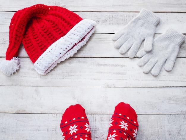 Selfie feet wearing red sock and handicraft santa claus hat on vintage wood