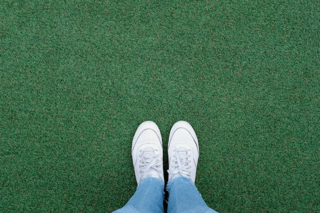 Selfie of feet in white sneakers shoes on green grass background with copy space, spring and summer with fashion lifestyle concept