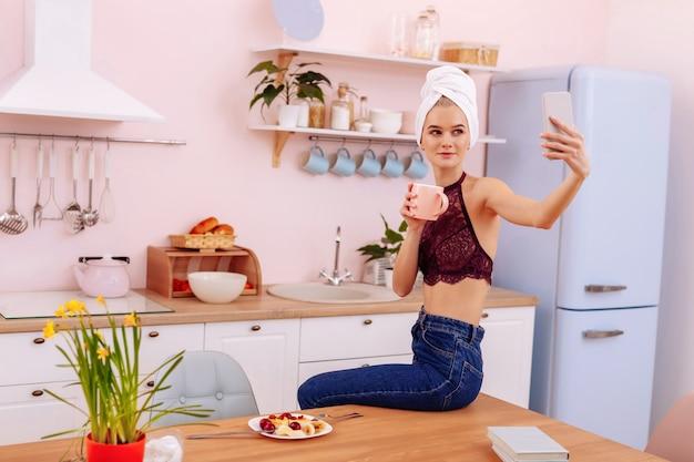 彼氏のための自分撮り。朝食を楽しみながら朝の彼氏のために自分撮りを作るスリムな女性