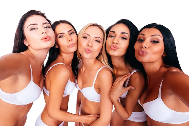 Selfie from beauties. five beautiful women in white lingerie making selfie while bonding to each other and against white background
