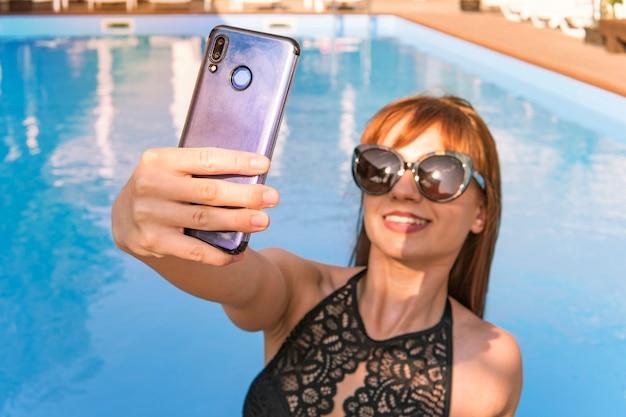 黒の水着姿の少女のスマートフォンからの自分撮り。休暇とテクノロジー。スイミングプールの近くで自分撮りの肖像画を撮るかなり若い女性のカラフルな肖像画