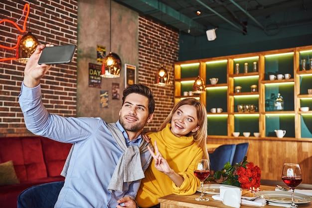 비싼 식당에서 셀카. 저녁 식사를 하면서 웃고 있는 젊은 부부가 전화로 셀카 사진을 찍고 있다