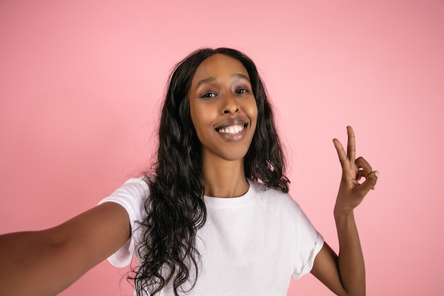 Selfie look. cheerful african-american young woman isolated on pink background, emotional and expressive. concept of human emotions, facial expression, sales, ad. beautiful model with long curly hair.
