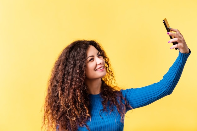 Одержимость селфи. зависимость от социальных сетей. современные технологии. девушка с помощью смартфона, чтобы сделать портретное фото.