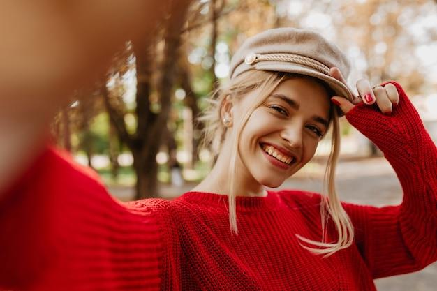 公園で微笑んでいる美しいブロンドのselfie。秋を楽しんでいる季節の服を着た見事な女性。