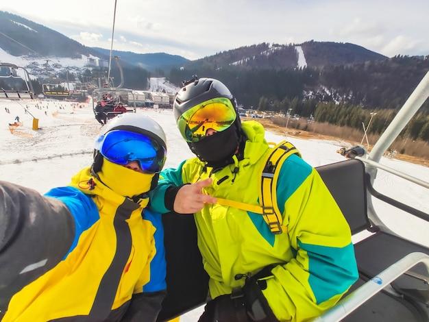 スキーリゾートの冬のアクティビティでカップルの自分撮り