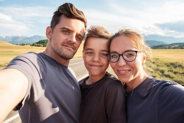 Селфи семьи в горах счастливые родители и концепция путешествия счастливый ребенок