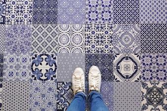 Selfie of feet with sneaker shoes on art pattern tiles floor background, top view