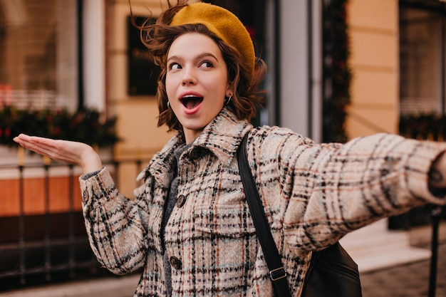 체크 무늬 코트에 재미있는 여자 학생의 selfie